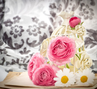 pink ranunculus flowers with vintage bird cage