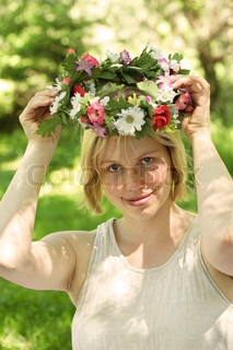 smiling summer girl holding garland over her head looking at camera