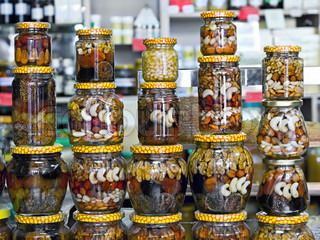 glass jars with nuts and honey on display in a store