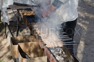 Man cook grilling meat on coal