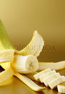 ripe banana cut into slices on a gold background