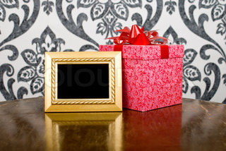 Golden photo frame and present box on table