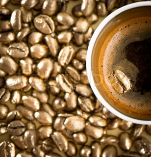 cup of black coffee with golden coffee beans