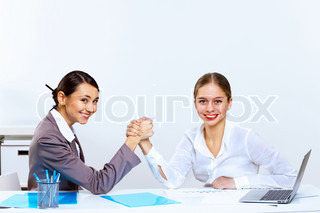 Young women arm wrestling in office
