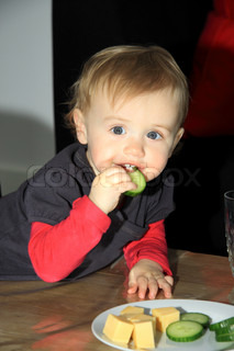 Small little girl learns eat cucumber