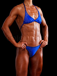 muscular woman posing against black background