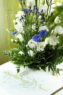 beautiful condolence bouquet with white and blue flowers over a card decorated with a cross