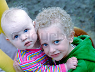 the white curly-headed boy with blue eyes and the his sister and their hands