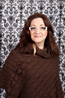 Brunette middle aged woman weather white framed glasses and feather hair extensions and accessories