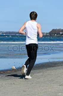 Athletic young male running on the beach From the back