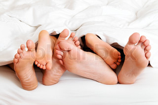 feet of a family in bed under the covers