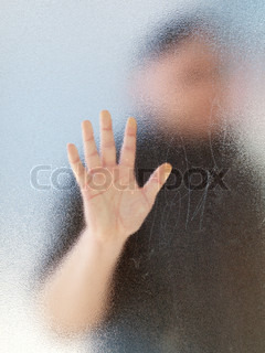 Silhouette of a man's body through frosted glassSilhouette of a man's body through frosted glass