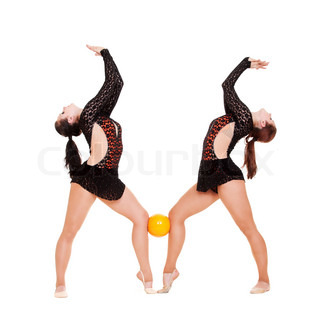 two smiley gymnasts posing with yellow ball