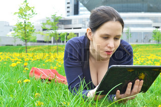 Young beauty student girl with tablet on nature background