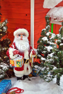 Santa Claus with gifts near the Christmas Tree