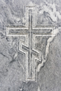 Closeup of orthodox cross carved in gravestone