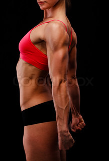 Muscular strong woman posing against a black background