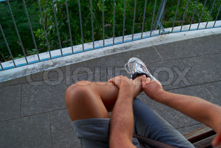naked tanned legs of male guy in sports shoes