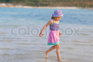 Little girl running at beach shore