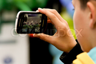 TERNOPIL, UKRAINE - MARCH 13: Boy is recording the show on opening new stadium to Euro 2012 on March 13, 2012 in Ternopil