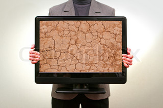 Man holding in hands lcd tv showing cracked clay ground