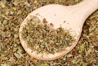 Pile of ground dried Basil Sweet Basil as background with wooden spoon Used as a spice in culinary herb all over the world The plant is also used in medicine