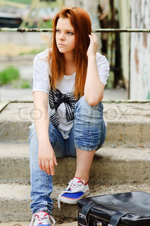 Beautiful young sad girl sitting on staircase