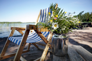 lazy striped folding chair and a can of windflowers on the beach in morning light