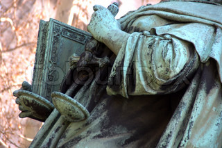statue of person holding a justice scales and a book