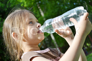 Girl drinking pure water in nature