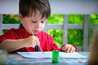Little boy painting with brush