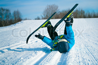 Boy with cross-country skis lying on his back in the snow