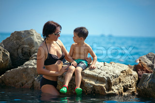 Mother talking with her son on a rocky seashore