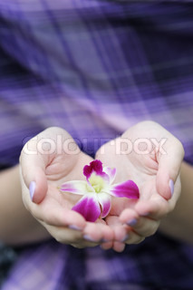 Woman holding beautiful lilac flower in her hands
