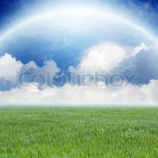 Peaceful background - green field, blue sky, white clouds, rainbow