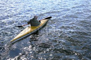 senior canoeist from above paddling in kayak in rippled blue water