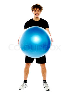 Male fitness trainer holding a pilate ball