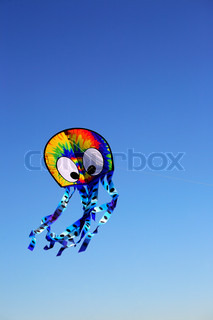 colourful  wind kite against clear blue sky, copy space