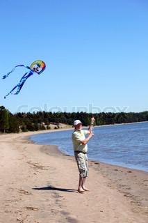 male pensioner flying wind kite on the seashore under clear blue sky