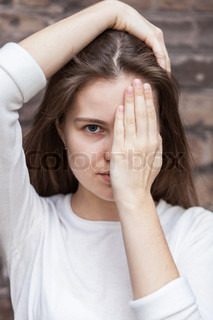Portrait young woman covering the half-face with his hand
