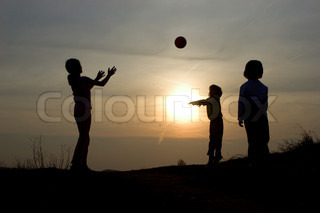 children by playing with the ball - silhouette