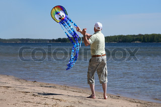 male senior struggling with wind kite on the beach
