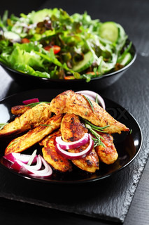Marinated chicken breast stripes with salad