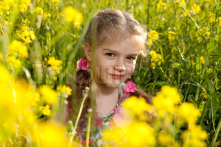 Little girl sitting in the grass and flowers