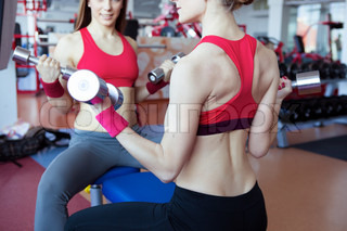 Two girls with dumbbell in fitness club