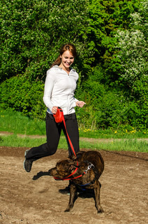 Woman walking with an American Stafford in the park