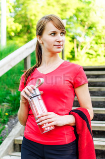 Portrait of female runner with bottle of water
