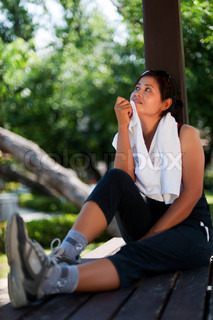 Middle-aged woman dressed in sportswear sitting on a bench in the park relaxing after sport with a towel around her shoulders