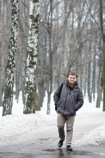 Middle age man walking in snow park