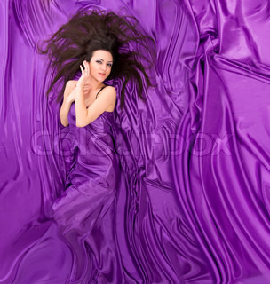 girl with long dark hair lying against a background of purple silk